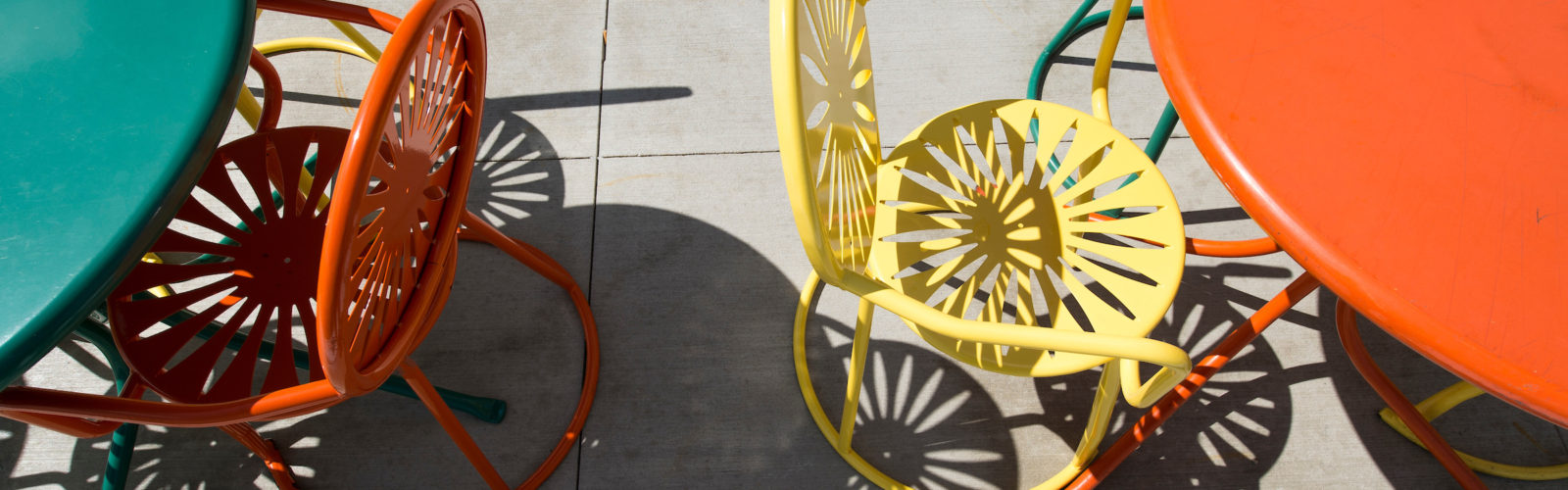 Shadows are cast from sun shining upon a group of Memorial Union Terrace chairs and tables at the University of Wisconsin-Madison during summer on July 1, 2014. The chairs are known for their iconic sunburst design. (Photo by Jeff Miller/UW-Madison)