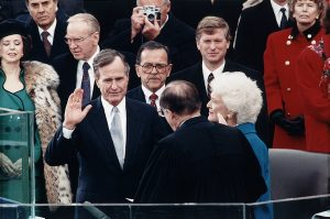 Chief Justice William Rehnquist administering the oath of office to George Bush on the west front of the U.S. Capitol, with Dan Quayle and Barbara Bush looking on, January 20, 1989