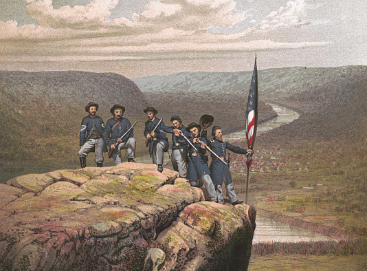 Union soldiers with an American flag standing on an overlook in Tennessee.