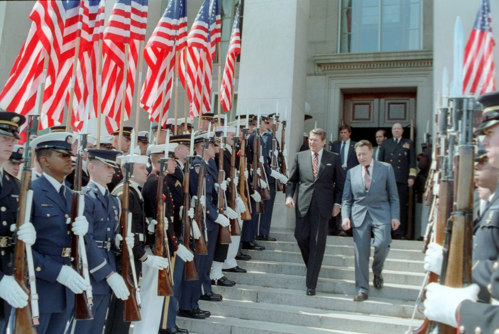 President Ronald Reagan and Caspar Weinberger Walking Past The Military and Us Flags During His Departure from The Pentagon